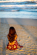 Long hair woman looking out at the ocean in the sand with long warm shadows late in the day in Da Nang watching the waves come in.