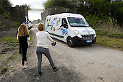 France, April 13th 2014: The Paris Roubaix 2014 publicity caravan throws copies of the La Voix du Nord newspaper to cycle fans at Pont Gibus, Wallers.