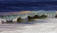 The spray from large winter waves refracts rainbow colors