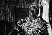 A black and white portrait of a Rendille tribe women inside her hut wearing beaded necklaces, Lake Turkana, Loiyangalani,Kenya, Africa