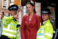 Policeman and Community Support Officer helping member of public; York; UK