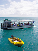 A glass bottom boat takes tourists on a reef tour at Green Island, along the Great Barrier Reef, near Cairns, QLD, Australia.