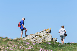 Holidaymakers standing on East Pentire Headland in Newquay, Cornwall.