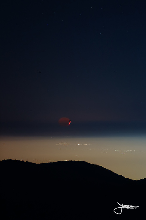 Waxing Crescent Moon sets in a fantastic scenery over the valley west of Granada. The shadow part of the moon is lit by Earthshine - Pradollano, Sierra Nevada, Spain