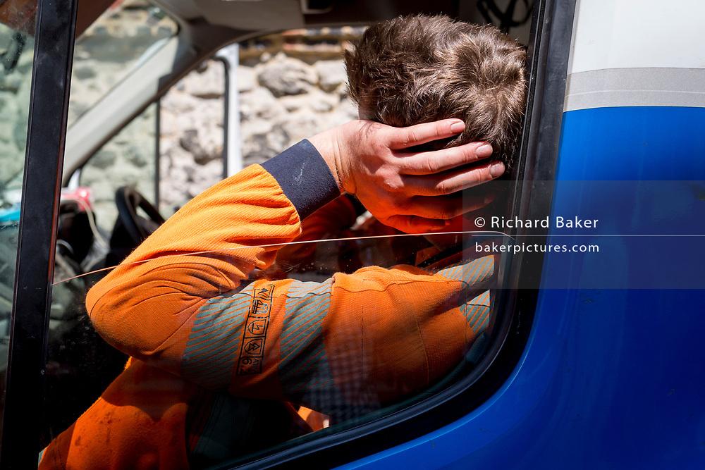 A Thames Water engineer rests in his van during repair works in Great College Street in Westminster, on 16th July 2019, in London, England.