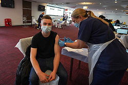 """© Licensed to London News Pictures. 10/07/2021. Sheffield, UK. Jack Beckkett,19, receives the first dose of the Pfizer/BioNTech vaccine at a pop-up vaccination clinic at Bramall Lane, home to Sheffield United football club in Sheffield, as part of the """"Grab a jab"""" campaign. Photo credit: Ioannis Alexopoulos/LNP"""