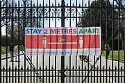 At the end of the second week of the UK government's Coronavirus lockdown, temperatures climb and local parks become busier (including Brockwell Park in Herne Hill - not pictured - which was closed due to 3,000 Londoners) crowded into the green space. Park users walk behind a Southwark council banner attached to gates of Dulwich Park, on 5th April 2020, in London, England.