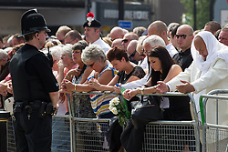 © Licensed to London News Pictures . 12/07/2013 . Bury , UK . Crowds gathered outside the church bow their heads in prayer during the service . The funeral for Fusilier Lee Rigby at Bury Parish Church in Bury town centre today (Friday 12th July 2013) , watched by 100s of people . Fusilier Rigby's coffin was held in Bury Parish Church overnight , watched over by an honour guard of soldiers from the 2nd Battalion Royal Regiment of Fusiliers ( 2RRF ) . Rigby was brutally murdered in Woolwich , London on 22nd May 2013 . Photo credit : Joel Goodman/LNP