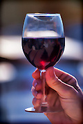 Photograph of a hand holding a wine glass