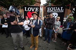 """© Licensed to London News Pictures . 16/08/2015 . Manchester , UK . Writer C P LEE amongst people reading an account of the """" Peterloo """" massacre at a memorial at the site of St Peter's Field , where fifteen people were killed during a cavalry charge on a democracy protest , 196 years ago (16th August 1819) . Photo credit : Joel Goodman/LNP"""