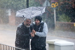 © Licensed to London News Pictures. 28/10/2020. London, UK. Men struggle to control an umbrella during heavy downpour in north London. Photo credit: Dinendra Haria/LNP