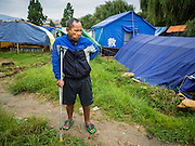 05 AUGUST 2015 - KATHMANDU, NEPAL: HOM BAHADUR LAMA, 52, walks through a large Internal Displaced Person (IDP) Camp in the center of Kathmandu. He is a farmer from Dolakha. His leg was injured in the earthquake. The camp is next to one the most expensive international hotels in Kathmandu. More than 7,100 people displaced by the Nepal earthquake in April live in 1,800 tents spread across the space of three football fields. There is no electricity in the camp. International NGOs provide water and dug latrines on the edge of the camp but the domestic waste water, from people doing laundry or dishes, runs between the tents. Most of the ground in the camp is muddy from the running water and frequent rain. Most of the camp's residents come from the mountains in northern Nepal, 8 - 12 hours from Kathmandu. The residents don't get rations or food assistance so every day many of them walk the streets of Kathmandu looking for day work.    PHOTO BY JACK KURTZ