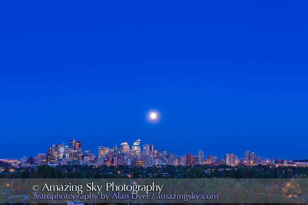 """The Full Moon of July 31 2015, an infamous """"Blue Moon,"""" rising over the skyline of Calgary, in a wide view taken with the 50mm lens and Canon 6D, as one frame of a 480-frame time-lapse. The location was Toronto Crescent."""