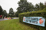 Extinction Rebellion climate activists lie in the road locked to fuel barrels to block an entrance to Farnborough Airport on 2nd October 2021 in Farnborough, United Kingdom. Activists blocked three entrances to the private airport to highlight elevated carbon dioxide levels produced by super-rich passengers using private jets and greenwashing by the airport in announcing a switch to sustainable aviation fuel SAF.
