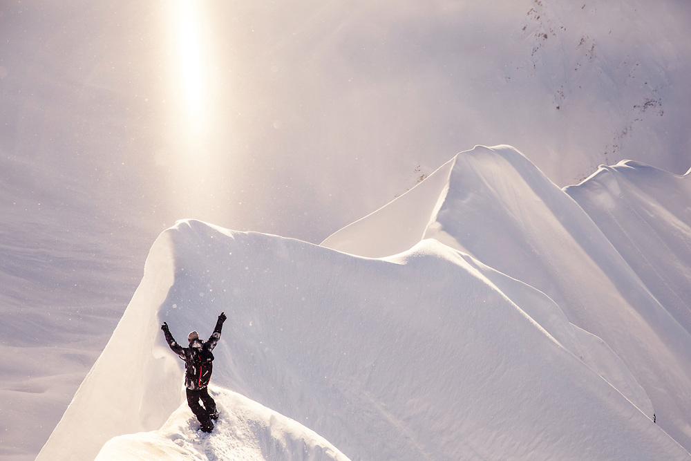 Glory Day<br /><br />2014 was an especially poor season in Alaska. It hadn't snowed much at all that year and most of the terrain we are used to riding was bare. After about ten days of waiting patiently in a backcountry cabin, our spirits at an all time low, a freak storm showed up on the radar and dropped enough snow to save our trip. This image of Travis Rice celebrating the new snow was shot at the top of our first run, when the sun broke out from the clouds creating the most beautiful light.