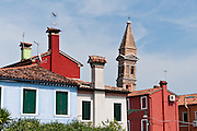 """The tilting campanile of the Church of San Martino contrasts with upright houses in Burano, Italy. Burano, known for knitted lacework, fishing, and colorfully painted houses, is a small archipelago of four islands linked by bridges in the Venetian Lagoon, northern Italy, Europe. Burano's traditional house colors are strictly regulated by government. The Romans may have been first to settle Burano. Romantic Venice (Venezia), """"City of Canals,"""" stretches across 100+ small islands in the marshy Venetian Lagoon along the Adriatic Sea in northeast Italy, between the mouths of the Po and Piave Rivers. Venice and the Venetian Lagoons are on the prestigious UNESCO World Heritage List."""