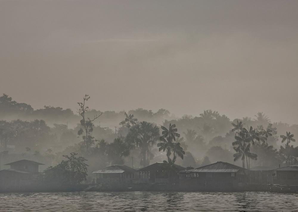 Saint-Georges de l'Oyapock, Guyane, 2015. <br />  <br /> Vue sur le quartier de l'invasion, extension d'Oiapoque face à Saint-Georges. Fleuve frontière et voie de communication naturelle entre les deux pays, l'Oyapock sépare la Guyane du Brésil. Ici, les riverains sont géographiquement, mais aussi culturellement ou économiquement plus proches de la rive opposée que de leurs capitales régionales. La France et le Brésil travaillent pourtant à l'achèvement d'une liaison routière qui reliera de façon terrestre la Guyane française à l'État brésilien de l'Amapà et plus globalement l'Union Européenne au Mercosul.