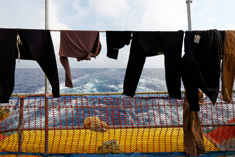 Wet clothes belonging to migrants hang to dry at the stern of the Medecins san Frontiere (MSF) rescue ship Bourbon Argos somewhere between Libya and Sicily August 8, 2015.  Some 241 mostly West African migrants on the ship are expected to arrive on the Italian island of Sicily on Sunday morning, according to MSF.<br /> REUTERS/Darrin Zammit Lupi <br /> MALTA OUT. NO COMMERCIAL OR EDITORIAL SALES IN MALTA