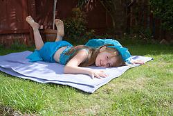 Little girl in fancy dress lying on a blanket in the garden,