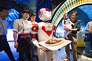 Robots serve customers with their food direct to their table. The waiters put the plate of food on the tray the robots hold and program the robot to move directly to the table. At the table another waiter takes off the food and gives it to the customer. Many customers enjoy this attraction and take pictures of the robots and selfies with them