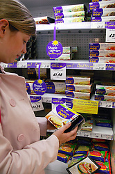 Woman checking fat content on a packet of convenience food,