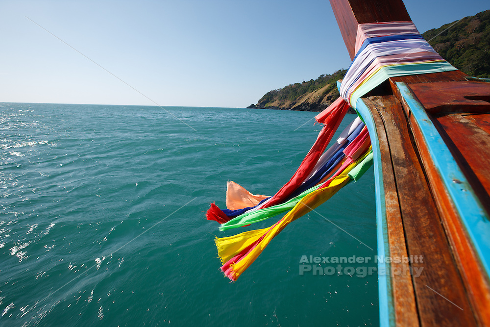 Longtail boat on the Andaman sea. Colorful scarves flapping in the wind honor the goddess of travel.
