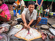 08 NOVEMBER 2014 - SITTWE, RAKHINE, MYANMAR:  A fish seller butchers a ray in the market in Sittwe. Sittwe is a small town in the Myanmar state of Rakhine, on the Bay of Bengal.  PHOTO BY JACK KURTZ