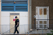 A police officer is seen patrolling the parameter of 12 Sutton Street  amid a full and total lockdown of 9 housing commission high rise towers in North Melbourne and Flemington during COVID-19 on 5 July, 2020 in Melbourne, Australia. After 108 new cases where uncovered overnight, the Premier Daniel Andrews announced on July 4 that effective at midnight last night, two more suburbs have been added to the suburb by suburb lockdown being Flemington and North Melbourne. Further to that, nine high rise public housing buildings in these suburbs have been placed under hard lockdown for a minimum of five days, effective immediately.  Residents in these towers will not be allowed to leave their units for any reason. Police will be stationed at every entry and exit point, every level, and they will also surround these locations preventing any movement in, or out. There is a total of 1354 units and over 3000 residents living in these buildings including the states most vulnerable people. These new restrictions will remain in place for fourteen days with fears of further lockdowns to come. The Government have stressed that if Victorians do not follow the basic COVIDSafe rules, the whole state will go back in to lockdown. (Image by Dave Hewison/ Speed Media)