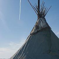 North of the Arctic Circle in Russia, a trans-polar jet flies over a chum (tepee) of the vanishing Komi reindeer herding people.