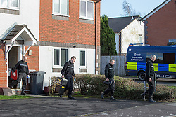 © Licensed to London News Pictures . 11/02/2014 . Blackburn , UK . Police with evidence bags and search tools leave a house at nearby 29 Florence Street . Police and forensic examiners on Emily Street in Blackburn at the scene where an eleven month old baby girl was mauled to death late last night (10th February 2014) . Photo credit : Joel Goodman/LNP