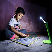 INDIVIDUAL(S) PHOTOGRAPHED: Raj Suresh Lohag. LOCATION: Patan, Satara District, Maharasthra, India. CAPTION: Instead of using an environmentally unfriendly and dangerous kerosene lantern, Raj now does his homework under the light of a small, portable solar-powered lamp that his mother purchased from one of Dharma Life's micro-entrepreneurs in their village.