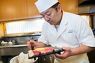 Sushi chef Masatoshi Yoshino is applying the nikiri shoyu (special soy sauce for sushi) on a clam nigiri sushi at his restaurant Yoshino Sushi Honten, Tokyo, Japan