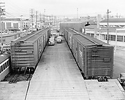 Y-490321-01. Hawthorne Freight Yards and buildings. Unloading shipment of new cars. March 21, 1949