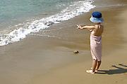Small girl wearing a summer hat, in Cala San Vicente, Ibiza, Balearic Islands, Spain