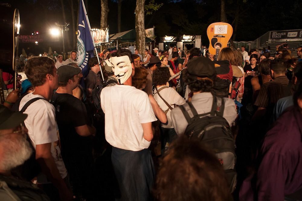 "A contingent from Occupy Wall Street prepares to leave after the concert. One member waves a guitar which bears the stcker ""Occupy Guitarmy 99""."