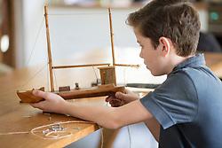 Boy Working on Model Ship