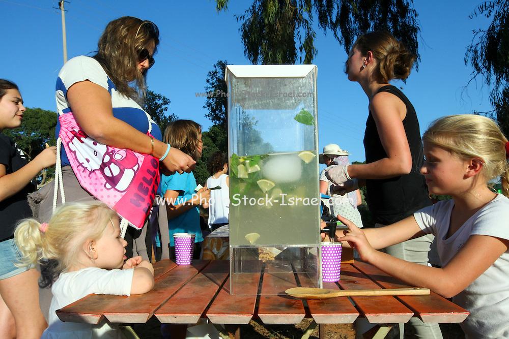 Children drink lemonade during outdoor activity