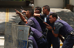 """Members of the Police take cover as they approach a group of Chavistas near the Cuban Embassy.  Opposition to President Hugo Chavez  gathered at the embassy to protest the recent arrests in Cuba as well as what they view as the """"cubanization"""" of Venezuela.  Chavez supporters also came to express their views and the two groups clashed, throwing rocks and bottles."""