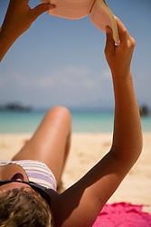 Close up of young woman reading book on beach