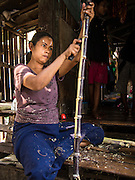 """28 FEBRUARY 2014 - MAE SOT, TAK, THAILAND: A Burmese woman peels sugar cane in front of her home. She sells sugar cane juice in the market in Mae Sot. Mae Sot, on the Thai-Myanmar (Burma) border, has a very large population of Burmese migrants. Some are refugees who left Myanmar to escape civil unrest and political persecution, others are """"economic refugees"""" who came to Thailand looking for work and better opportunities.    PHOTO BY JACK KURTZ"""