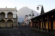 Volcan de Agua, the Volcano of Water, 3766m, dominates views to the south of Antigua Guatemala. Here it is the background to 5 Avenida Sur and Parque Central. The end of the Palacio de los Capitanes Generales is on the left. Antigua Guatemala, Republic of Guatemala. 02Mar14