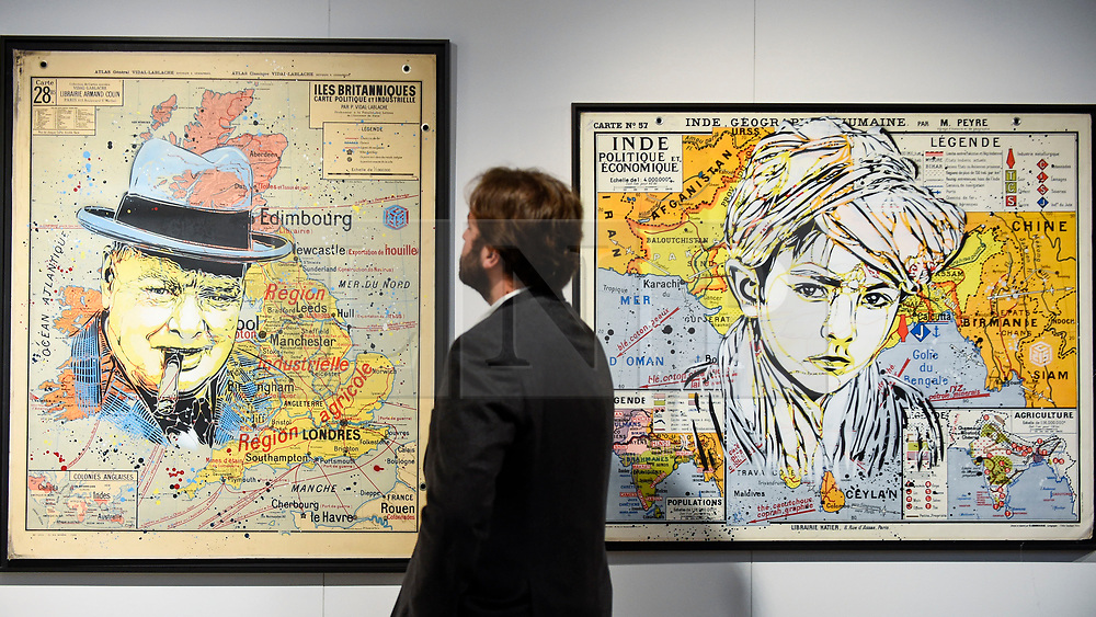 """© Licensed to London News Pictures. 04/10/2019. LONDON, UK. A staff member views (L to R) """"Churchill"""", 2019, and """"Turban Kid"""", 2019, both by C215 at the Mazel Galerie stand at Moniker International Art Fair, an urban contemporary art fair taking celebrating its 10 year anniversary in the UK.  The fair is  place at Chelsea's Sorting Office air until 6 October 2019.  Photo credit: Stephen Chung/LNP"""