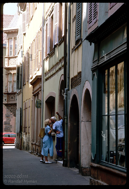 Woman whispers parting words to man in doorway of apartment bldg in alleyway; Colmar, Alsace France