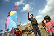 Ehsan, 13, the eldest son of Noor Agha, center, flies a kite along with other siblings next to his house, Kabul, Afghanistan, Saturday, March, 10, 2007. Noor Agha is a renowned kite maker who made kites for the movie makers of the best-selling novel, The Kite Runner, which will be distributed by Dreamworks and Paramount Vantage in Nov. this year. Noor Agha's wives, using their special glue, help him produce enough kites to please the clients' needs. Some of his children can also make their own kites with plastic bags and bamboo sticks. As the Afghan New Year's Day (Nawruz) approaching on March 21, the finger tips of Noor Agha's family got busier for mass production.