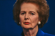 Prime Minster Margaret Thatcher is seen giving a party speech at the 1991 Conservative Party Conference in Blackpool, Lancashire, a full year after being removed by her own colleagues the previous November. Her softer and perhaps pensive expression contrasts with her reputation of the Iron Lady with a gaze that made her opponents uncomfortable. She seems distant here, perhaps recalling her great days in office when she was a powerful figure in world politics. She is wearing the same favourite two-tone blue suit with wide shoulders and a pearl ear-rings as she wore the year before when still in office. The ambient stage lights emphasize the blonde highlights in her hair.