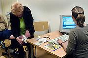 Nederland, Nijmegen, 11-7-2005..Een arts, huisarts, van de huisartsenpost, huisartsendienst, werkt per computer de patientengegevens bij van een patient. Administratie, papierwerk. Spreekkamer. Avonddienst, bereikbaarheid, spoedgeval, ongelukje. Gezondheidszorg, eerstelijns zorg. Zorgverzekeraar, zorgverzekering. Basispakket. Basisverzekering...Foto: Flip Franssen
