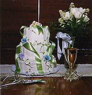 Wedding cake with champagne glasses and white roses.