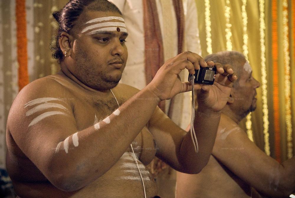 Pujari taking photo in his mobile during South Indian Traditional Tamil Brahmin Wedding