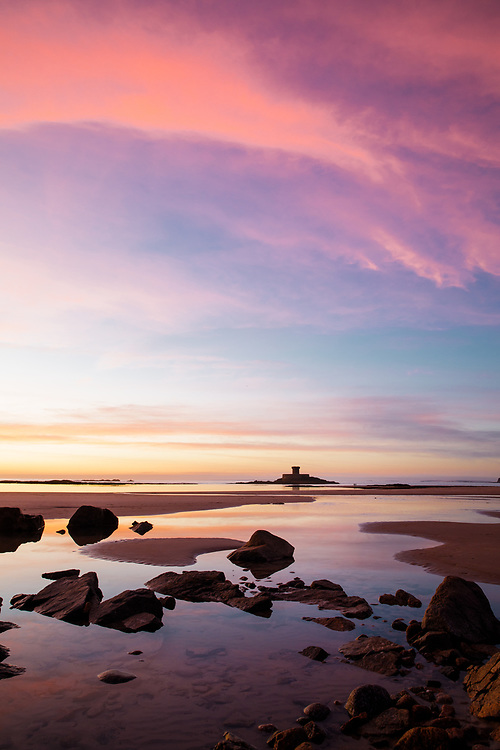 Pink sky reflecting in rock pools and streams of water leading to the sea at sunset at La Rocco Tower, St Ouen's Bay, Jersey, Channel Islands