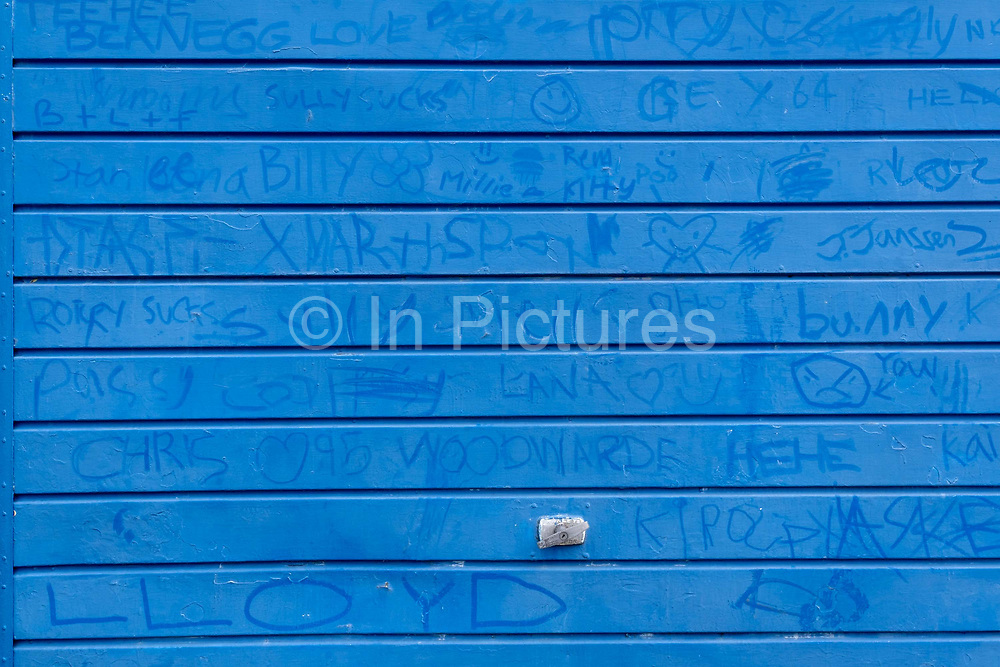 The names of local children are written on the grubby surface of a garage door in Dulwich, south London, on 8th December 2020, in London, England.